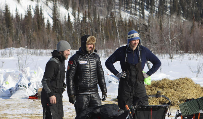 Past Iditarod champions Joar Ulsom, right, and Pete Kaiser pose for a photo with Richie Diehl, left, in the Ophir, Alaska, during the Iditarod Trail Sled Dog Race on Friday, March 12, 2021. The three are close friends and have been traveling close together for sections of the race. (Zachariah Hughes/Anchorage Daily News via AP, Pool)