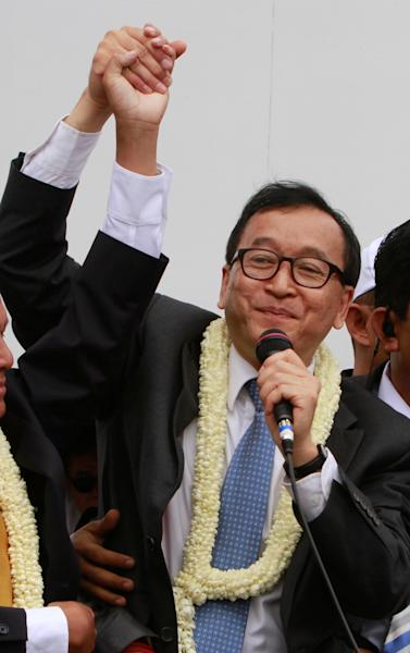 Sam Rainsy, president of Cambodia National Rescue Party (CNRP) greets his supporters on his arrival at Phnom Penh International Airport, in Phnom Penh, Cambodia, Friday, July 19, 2013. Thousands of cheering supporters greeted Cambodian opposition leader Sam Rainsy as he returned from self-imposed exile Friday to spearhead his party's election campaign against well-entrenched Prime Minister Hun Sen. (AP Photo/Heng Sinith)