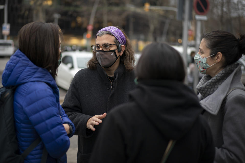 "Victoria Martinez, 44, speaks with other mothers at the gates of her daughters' school, one of the few public spaces where she dares to socialize, in Barcelona, Spain, Wednesday, Feb. 10, 2021. By May this year, barring any surprises, Martinez will complete a change of both gender and identity at a civil registry in Barcelona, finally closing a patience-wearing chapter that has been stretched during the pandemic. The process, in her own words, has also been ""humiliating."" (AP Photo/Emilio Morenatti)"