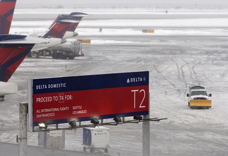 A snowplow makes its way on a slushy patch between two terminals after a Delta flight from Toronto to New York skidded off the runway into snow at Kennedy International Airport, temporarily halting all air travel into and out of the airport, Sunday, Jan. 5, 2014, in New York. (AP Photo/Kathy Willens)
