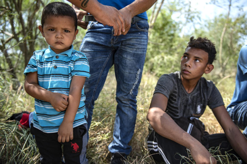 Children wait to be searched after being detained by Border Patrol