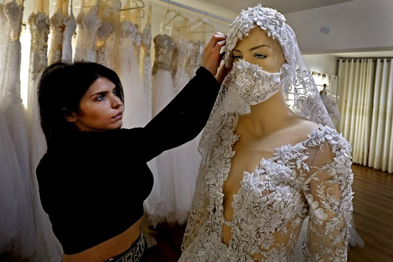 ISRAEL: Lobna Safadi, shown inside her workshop in the Druze village of Majdal Shams, attaches a matching embroidered mask to a wedding dress she designed.