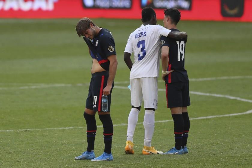 Honduras' Wesly Decas, center, comforts United States' Sebastian Soto, right, beside Ulysses Llanez at the end.