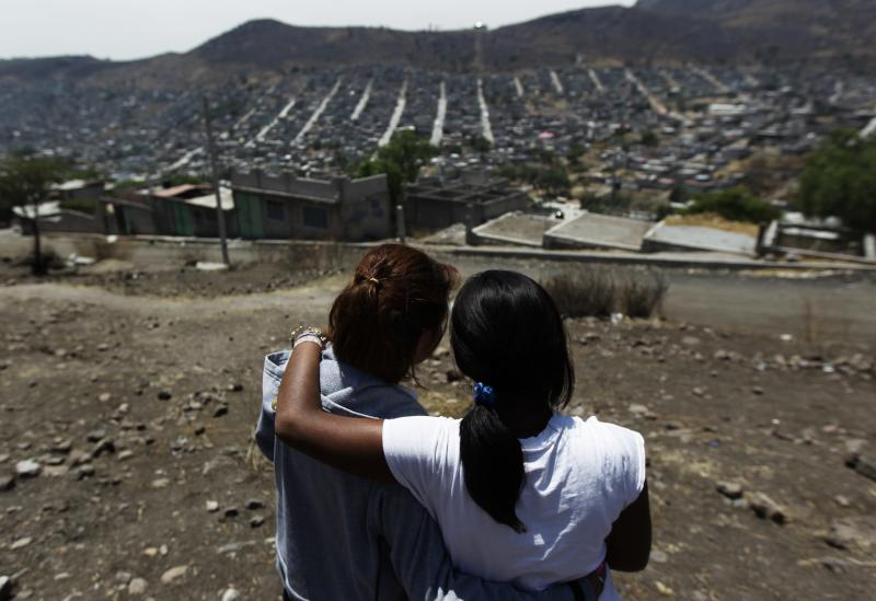 Girls who had suffered sexual abuse embrace each other while standing on a hill side where the dead bodies of sexually abused women were found on several occasions in Ecatepec