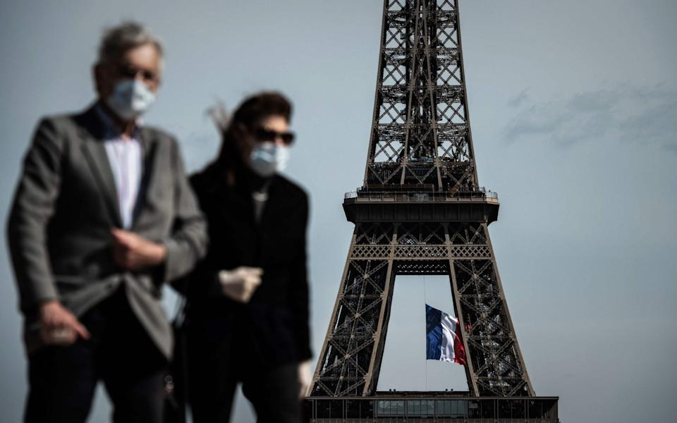 A man and a woman wearing face masks walk on Trocadero Plaza as a French national flag flies on the Eiffel Tower - AFP