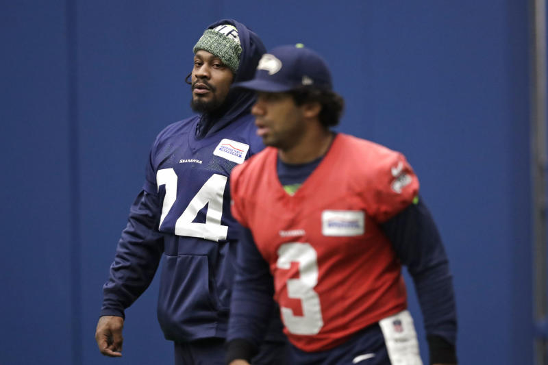 Seattle Seahawks running back Marshawn Lynch, left, looks across at quarterback Russell Wilson during warmups at practice this week. (AP Photo/Elaine Thompson)