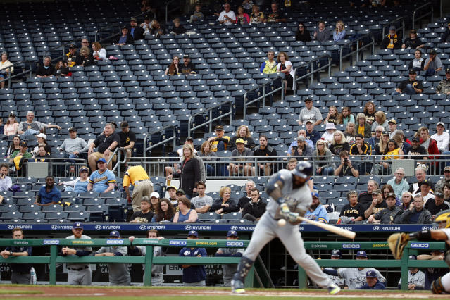 Fans and Milwaukee Brewers watch as Brewers' Eric Thames swings at a third strike from Pittsburgh Pirates starting pitcher Joe Musgrove to end the top of the first inning of a baseball game in Pittsburgh, Thursday, May 30, 2019. (AP Photo/Gene J. Puskar)