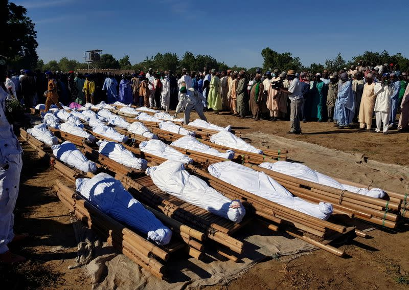 Men gather near dead bodies of people who were killed by militant attack, during a mass burial at Zabarmari