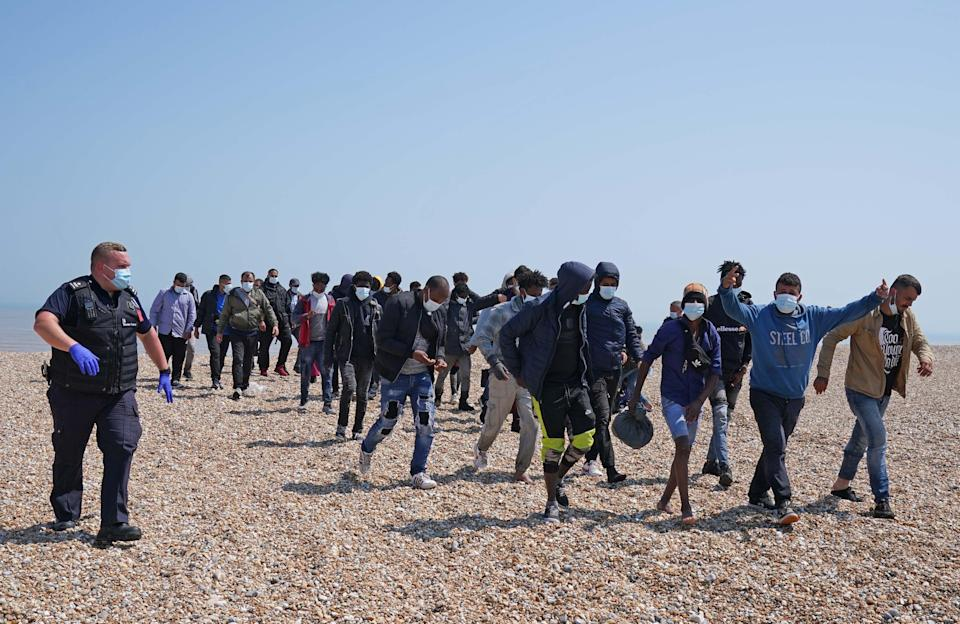A group of people thought to be migrants are escorted from the beach in Dungeness, Kent (Gareth Fuller/PA) (PA Wire)