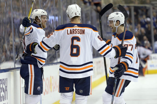 Edmonton Oilers center Connor McDavid, left, celebrates his goal against the Toronto Maple Leafs with defensemen Adam Larsson (6) and Oscar Klefbom (77) during third-period NHL hockey game action in Toronto, Monday, Jan. 6, 2020. (Nathan Denette/The Canadian Press via AP)
