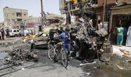 A boy walks past with his bicycle near the site of a car bomb in Baghdad's Sadr City, August 1, 2014. Violence killed 1,737 people, mostly civilians, in Iraq in July, when Sunni insurgents seized large swathes of land in the north, United Nations figures showed. REUTERS/Wissm al-Okili (IRAQ - Tags: CIVIL UNREST POLITICS)