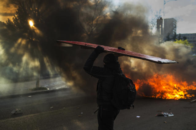 <p>A student brings wood to a fire started by student protesters during the first day of a strike against government cutbacks in education, Complutense University, Madrid, March 26, 2014. (AP Photo/Andres Kudacki) </p>