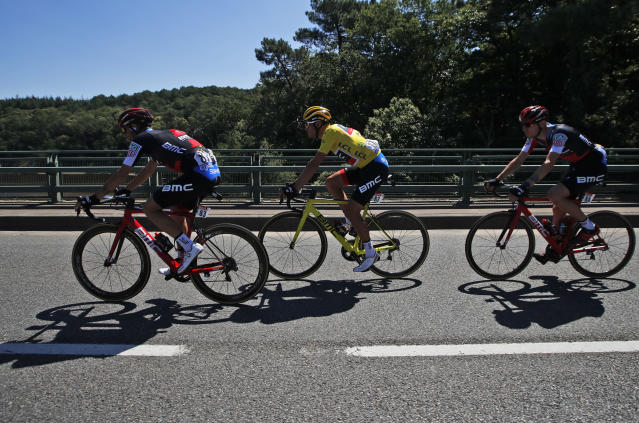 Belgium's Greg van Avermaet, wearing the overall leader's yellow jersey, rides with his teammates Italy's Damiano Caruso, left, and Tejay van Garderen of the U.S., right, during the fifth stage of the Tour de France cycling race over 204.5 kilometers (127 miles) with start in Lorient and finish in Quimper, France, Wednesday, July 11, 2018. (AP Photo/Christophe Ena )