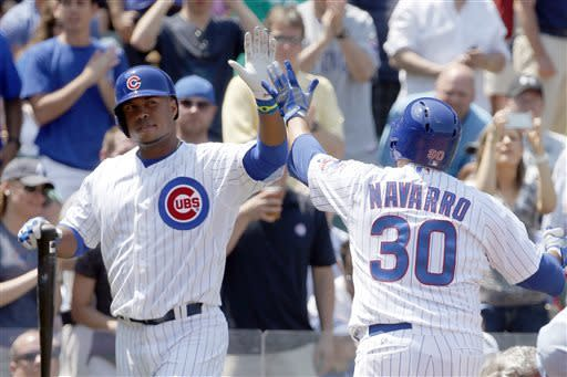 Chicago Cubs' Scott Hairston, left, greets Dioner Navarro (30) at home after Navarro's home run off Chicago White Sox starting pitcher John Danks during the second inning of a interleague baseball game Wednesday, May 29, 2013, in Chicago. (AP Photo/Charles Rex Arbogast)
