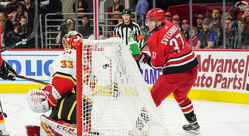 RALEIGH, NC - OCTOBER 29: Carolina Hurricanes Left Wing Andrei Svechnikov (37) uses a lacrosse move to lift the puck behind Calgary Flames Goalie David Rittich (33) during a game between the Calgary Flames and the Carolina Hurricanes at the PNC Arena in Raleigh, NC on October 29, 2019. (Photo by Greg Thompson/Icon Sportswire via Getty Images)