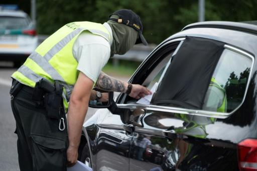 A Slovak police officer checks the papers of a motorist
