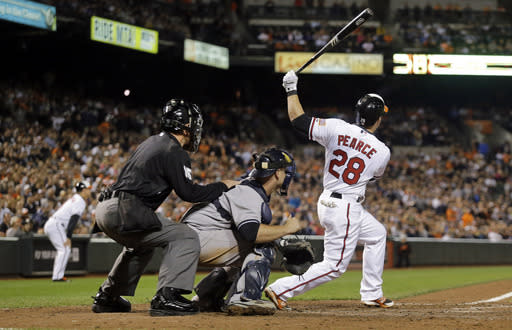 Baltimore Orioles' Steve Pearce, right, doubles in front of New York Yankees catcher Brian McCann and home plate umpire Ed Hickox in the ninth inning of a baseball game, Sunday, Sept. 14, 2014, in Baltimore. Quintin Berry scored on the play to tie the game. Baltimore won 3-2. (AP Photo/Patrick Semansky)
