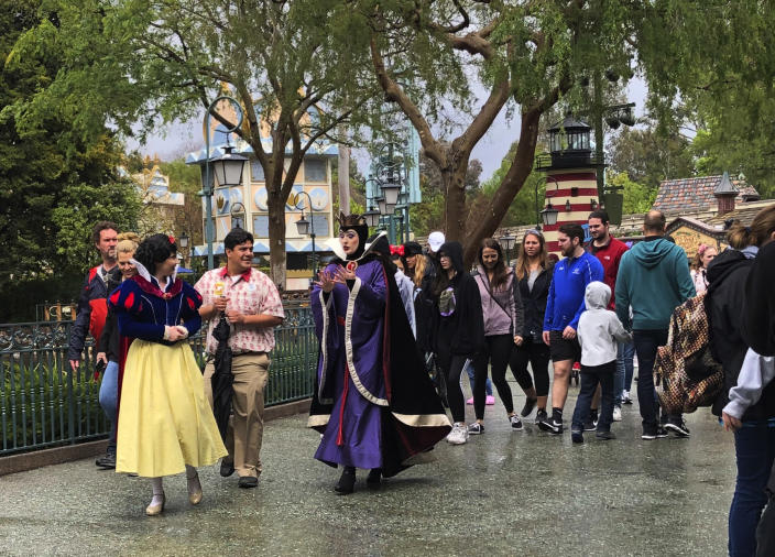 A visitor around at Disneyland in Anaheim, Calif. on Friday, March 13, 2020. Disneyland is closing its doors for the rest of the month, shuttering one of California's best-known attractions as the state hurries to stop the spread of the coronavirus. (AP Photo/Amy Taxin)