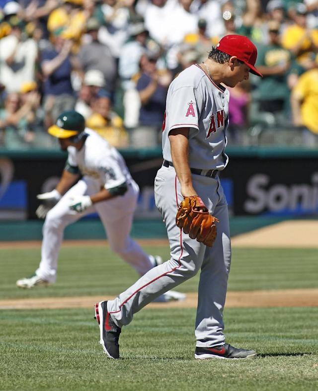 Los Angeles Angels pitcher Jason Vargas, front, looks down as Oakland Athletics' Coco Crisp rounds third base after hitting a two-run home run in the third inning of a baseball game, Wednesday, Sept. 18, 2013, in Oakland, Calif. (AP Photo/George Nikitin)