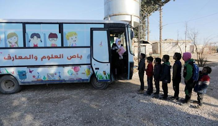 Sudents wait in line to attend a class inside a bus in the city of al-Bab