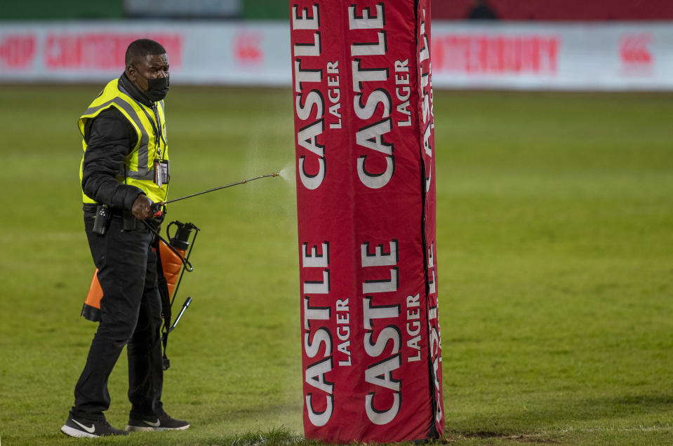 A stadium worker sanitises safety pads attached to the goal post during half-time of a warm-up rugby match between South Africa's Sharks and British and Irish Lions at the Loftus Versfeld stadium in Pretoria, South Africa, Saturday, July 10, 2021. (AP Photo/Themba Hadebe)