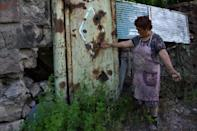 Evelina Hovhanisyan, 70, points out the damage caused by shelling in a village in the Tavush region of Armenia