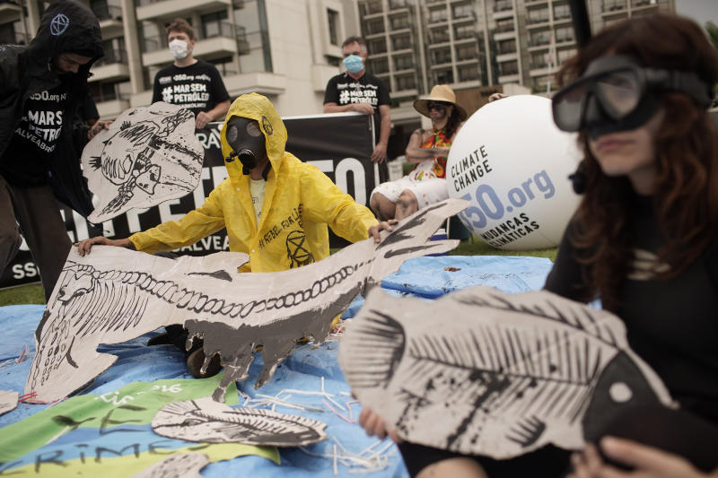 Demonstrators protest against the auction for the exploration of oil fields close to Abrolhos, a marine national park in Bahia state, in Rio de Janeiro, Brazil, Thursday, Oct. 10, 2019. Under pressure from environmental organizations, none of the 17 companies involved in the process presented any offers. (AP Photo/Silvia Izquierdo)