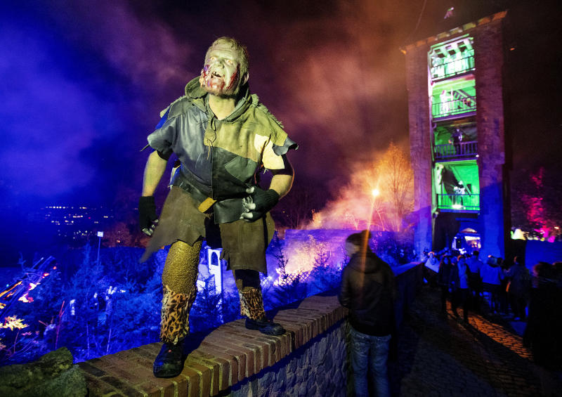 An actor stands on a wall of the medieval Frankenstein Castle about 35 kilometers (22 miles) south of Frankfurt, Germany Saturday, Oct. 26, 2019. The Medieval Frankenstein Castle has become a favorite haunt for Germans celebrating Halloween, a tradition that's become increasingly popular in continental Europe in recent years. The crumbling castle, located about 35 kilometers (22 miles) south of Frankfurt, has been staging spooky festivals since 1977 featuring monsters, gore and spine-chilling live shows. (AP Photo/Michael Probst)