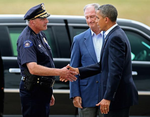 President Barack Obama (R) is greeted by Aurora Police Chief Dan Oates (L) and Aurora Mayor Steve Hogan after arriving at Buckley Air Force Base July 22, 2012 in Aurora, Colorado. Obama traveled to the University of Colorado Hospital to meet with victims of last Friday's movie theater mass shooting. Police in Aurora, a suburb of Denver, say that James Holmes, 24, in custody after he is suspected of killing 12 people and injuring 59 during a midnight screening of 'The Dark Knight Rises' last Friday. (Photo by Chip Somodevilla/Getty Images)