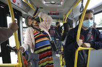 """Marlene Alfonso, a 69-year-old Venezuelan grandmother who goes by the name """"Toothless Cindy,"""" sings about Venezuelan migrants' lives in hopes of tips from commuters on the Transmilenio, the crowded and crime-ridden public bus system in Bogota, Colombia, Tuesday, Nov. 3, 2020. Alfonso suffers from glaucoma and cannot see out of her left eye, thus can't see the buttons on her speaker's remote control properly, so she asks commuters for help to play the right tracks. (AP Photo/Fernando Vergara)"""