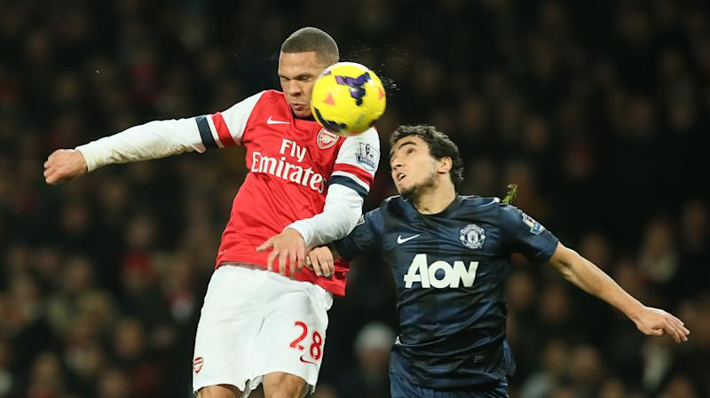 Arsenal's Kieran Gibbs, left, challenges for the ball as he out jumps Manchester United's Rafael during their English Premier League soccer match between Arsenal and Manchester United at the Emirates stadium in London, Wednesday, Feb. 12, 2014. (AP Photo/Alastair Grant)