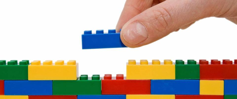 hand building up a wall by stacking up lego.