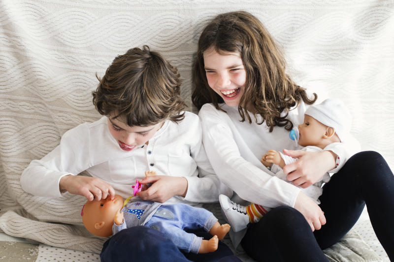 Boy and girl playing with dolls