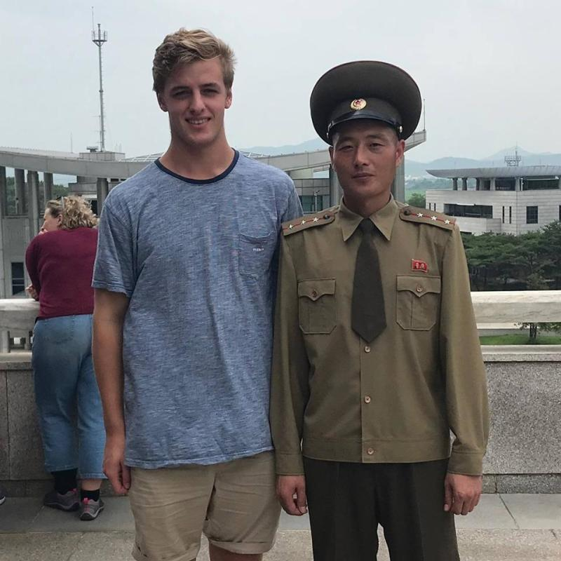 Alex snapped a picture with an army guard during a brave visit to North Korea last year. Photo: Facebook