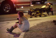 <p>A woman sits on a curb at the scene of a shooting outside of a music festival along the Las Vegas Strip, Monday, Oct. 2, 2017, in Las Vegas. Multiple victims were being transported to hospitals after a shooting late Sunday at a music festival on the Las Vegas Strip. (AP Photo/John Locher) </p>