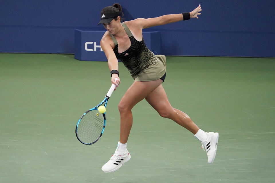 Garbine Muguruza, of Spain, returns a shot to Andrea Petkovic, of Germany, during the second round of the US Open tennis championships, Wednesday, Sept. 1, 2021, in New York. (AP Photo/Seth Wenig)