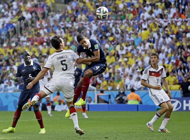 Germany's Mats Hummels heads the ball past France's Raphael Varane to score his side's first goal during the World Cup quarterfinal soccer match at the Maracana Stadium in Rio de Janeiro, Brazil, Friday, July 4, 2014. (AP Photo/Kirsty Wigglesworth)