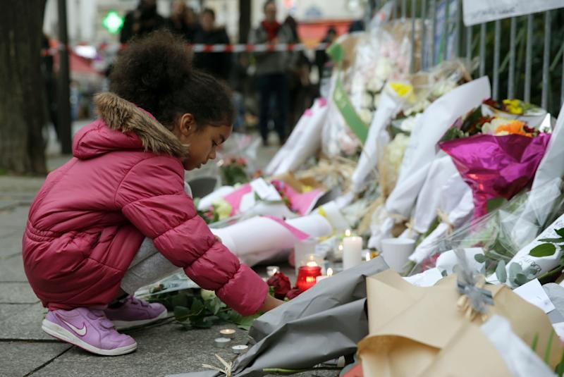 A child puts a candle near flowers along a rail cordon close to the Bataclan theatre in the 11th district of Paris, on November 14, 2015