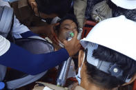 In this image from a video, medics attend to a man in a street in Dawei, Myanmar Sunday, Feb. 28, 2021. The man appeared to be a wound in his upper chest. Medics held an oxygen mask to his face while calling out for an ambulance. (Dakkhina Insight via AP)
