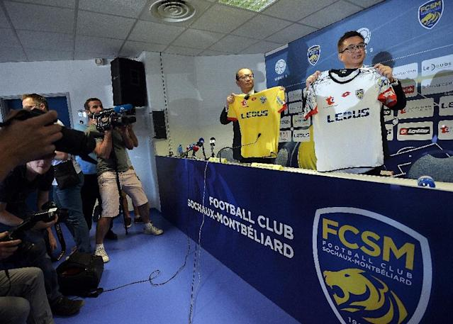 Li Wing-Sang (C), CEO of Hong-Kong based company Ledus, and financial director Chi Hung Chiu (R) show the new jerseys of Sochaux's football club on July 6, 2015 during a press conference at the Auguste Bonal stadium in Montbeliard (AFP Photo/Patrick Hertzog)