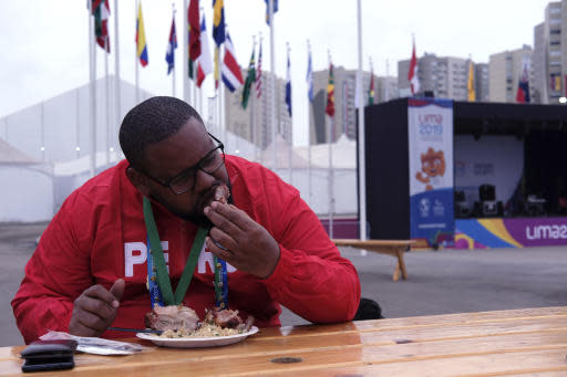 In this Aug. 8, 2019 photo, Rodrigo Rosa, a Brazilian who worked for the event organizing at the Pan American Games eats pork and chaufa fried rice at the international center outside the Pan American athletes' village in Lima, Peru. Peruvian food was the star at the recent Pan Am Games held in Latin Americas culinary capital. Athletes from countries across the Americas tasted the highly-regarded cuisine that blends indigenous traditions with European, African and Asian influences with an abundance of seafood from the Pacific Oceans cold Humboldt current. (AP Photo/Luis Andres Hena