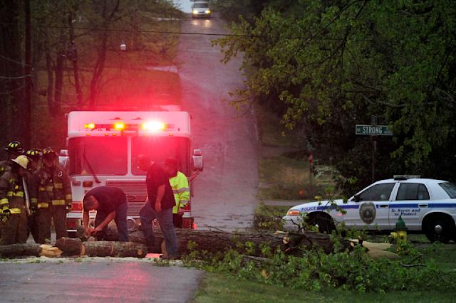 Huntsville Fire and Rescue crews remove a downed tree blocking traffic on Dell Avenue as strong storms passed through Huntsville, Ala. Thursday, April 11, 2013. A strong spring storm that socked the Midwest with ice and heavy, wet snow made its way east, raking the South with tornadoes Thursday, with three deaths blamed on the rough weather and thousands of people without power. (AP Photo/AL.com, Eric Schultz)