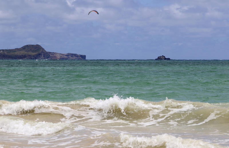 """In this May 15, 2019, photo, a kitesurfer rides off Kailua Beach Park in Kailua, Hawaii. In Kailua, the sand is soft and white, the water is clear and calm, and the view is exactly what you might expect from a beach in the Hawaiian Islands. Those are among the reasons the beach has been selected as the best stretch of sand on an annual list of top U.S. beaches. Stephen Leatherman, a coastal scientist and professor at Florida International University, has been drafting the list under the alias """"Dr. Beach"""" since 1991. (AP Photo/Caleb Jones)"""