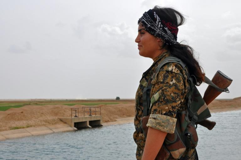 A female fighter from the Syrian Democratic Forces stands near Tishreen Farms, north of Raqa on May 2, 2017