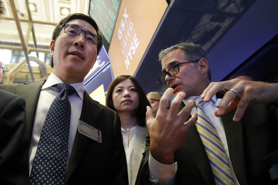 GSX Techedu Chairman and CEO Larry Xiangdong Chen, left, and company CFO Nan Shen, meet with specialist Anthony Rinaldi during their IPO at a trading post on the floor of the New York Stock Exchange, Thursday, June 6, 2019. (AP Photo/Richard Drew)