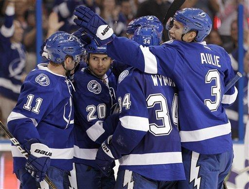 Tampa Bay Lightning right wing Tim Wallace (20) celebrates with teammates, including left wing Tom Pyatt (11), right wing J.T. Wyman (34) and defenseman Keith Aulie (3), after scoring against the Ottawa Senators during the second period of an NHL hockey game Tuesday, March 6, 2012, in Tampa, Fla. (AP Photo/Chris O'Meara)