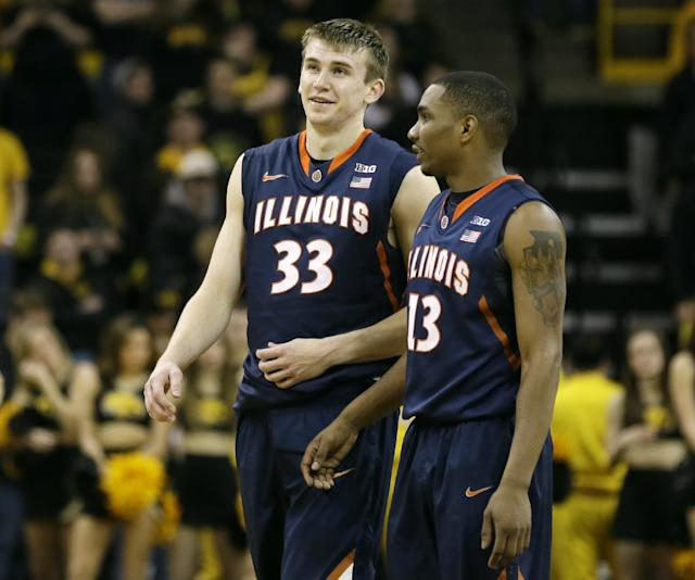 Illinois forward Jon Ekey, left, smiles with teammate Tracy Abrams at the end of an NCAA college basketball game against Iowa, Saturday, March 8, 2014, in Iowa City, Iowa. Ekey made a 3-point basket in the final seconds to give Illinois a 66-63 victory. (AP Photo/Charlie Neibergall)