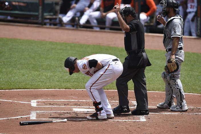 Baltimore Orioles' Ryan Mountcastle, left, reacts after getting hit on the hand by a pitch in the first inning of a baseball game against the Chicago White Sox, July 11, 2021 in Baltimore.(AP Photo/Gail Burton)