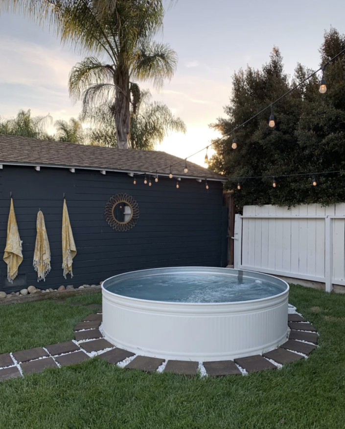 """<p>Hang string lights above your stock tank pool to create the perfect backyard oasis. </p><p><strong>See more at</strong> <strong><a href=""""https://www.arrowsandbow.com/diy-stock-tank-pool"""" rel=""""nofollow noopener"""" target=""""_blank"""" data-ylk=""""slk:Arrows + Bow"""" class=""""link rapid-noclick-resp"""">Arrows + Bow</a>.</strong></p><p><a class=""""link rapid-noclick-resp"""" href=""""https://www.amazon.com/Backyard-Hanging-Outdoor-Pergola-Deckyard/dp/B00RQHBZVS/ref=sr_1_12?tag=syn-yahoo-20&ascsubtag=%5Bartid%7C10050.g.3404%5Bsrc%7Cyahoo-us"""" rel=""""nofollow noopener"""" target=""""_blank"""" data-ylk=""""slk:SHOP STRING LIGHTS"""">SHOP STRING LIGHTS</a></p>"""
