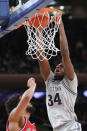 Georgetown center Qudus Wahab (34) dunks in front of St. John's guard LJ Figueroa during the first half of an NCAA college basketball game in the first round of the Big East men's tournament Wednesday, March 11, 2020, in New York. (AP Photo/Kathy Willens)